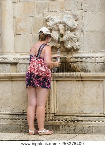 Dubrovnik, Croatia - August 3 2018: Female Tourist Getting Water At Fountain