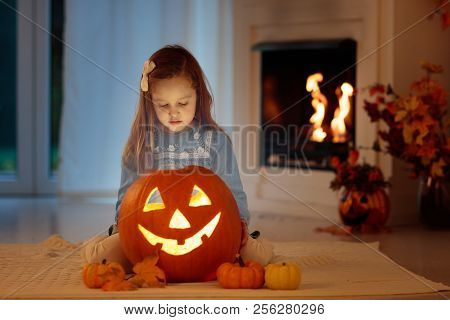 Kids Carving Pumpkin On Halloween At Home Sitting Next To Fireplace In Living Room Decorated With La