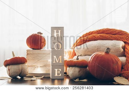 Background With Warm Sweaters And The Inscription Home. Pile Of Knitted Clothes With Autumn Leaves,