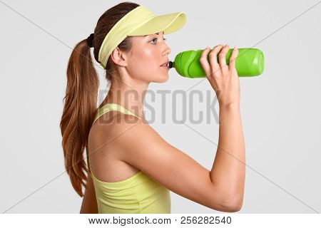 Sideways Shot Of Exhausted Female Tennis Player Drinks Cold Water From Bottle, Takes Break After Lon