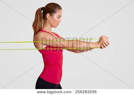 Sideways Shot Of Determined Sportswoman Makes Stretching Exercise With Fitness Gum, Works On Muscles