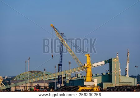 Heavy Crane And Buildings And Industrial Warehouses In Port Facilities