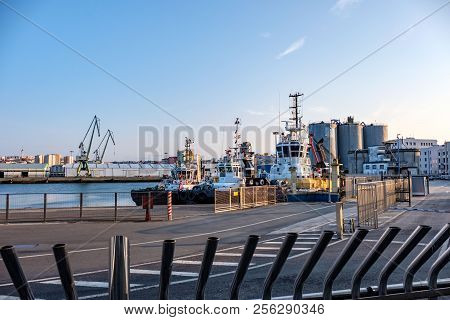View Of Three Tug Boats Moored In Port And Facilities Cranes And Silos