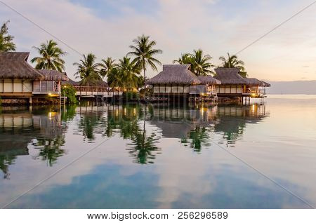 Overwater Bungalows At Sunset In Moorea, French Polynesia