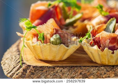 Exquisite Beautiful Serve Prosciutto In Baskets On A Wooden Slice.