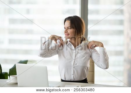 Smiling Businesswoman Doing Office Exercises To Relieve Shoulder