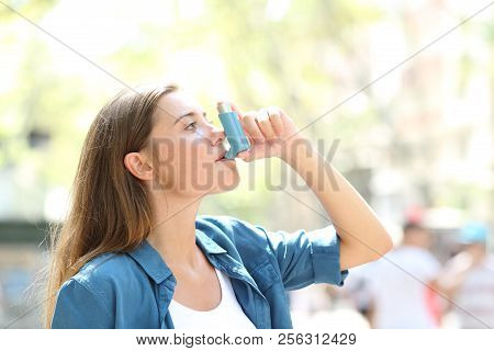 Side View Portrait Of An Asthmatic Woman Using A Inhaler Outdoors In The Street