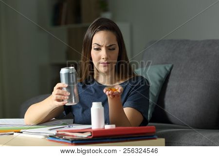 Suspicious Student Comparing Vitamin Pill Supplement And Energy Drink Trying To Decide At Home In Th