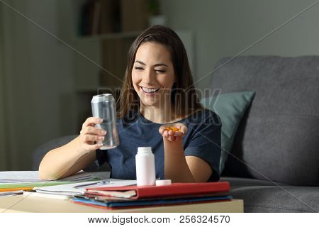 Happy Student Deciding Between Energy Drink And Vitamin Supplement Pills In The Night At Home