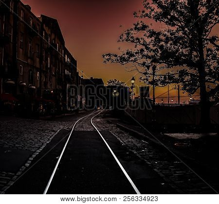 The Riverfront In As Night Falls And An Automobile Turns Onto The Trolly Track In The Brick Road In