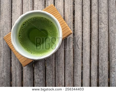 Top View Of Organic Green Tea Matcha With Heart Shape In Foam  In White Japanese Style Ceramic Bowl