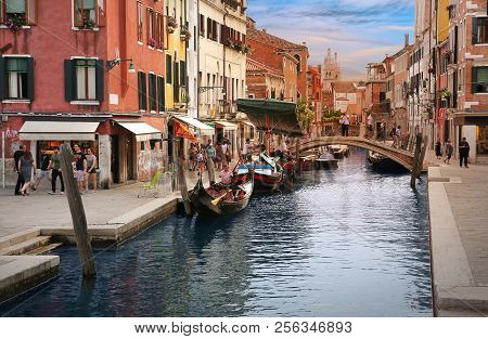 Venice, Italy, Jun 7 2018: Classic Venetian View With Gondolier On His Gondola In A Small Canal Surr