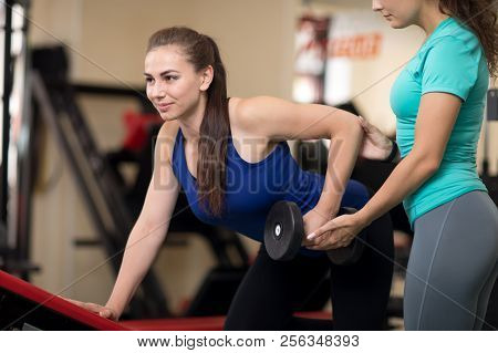 Personal Trainer Helping Sporty Woman With Weight Training Equipment In Gym
