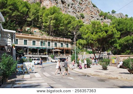 MAJORCA, SPAIN - SEPTEMBER 6, 2017: Tourists walk in the port town of Sa Calobra on the Spanish island of Majorca. The town is home to the tourist attraction of the Torrent de Pareis canyon.