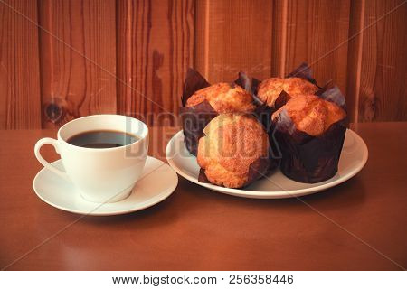 Coffee And Vanilla Muffins On Wooden Table