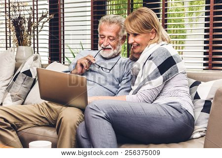 Senior Couple Relaxing And Using Laptop Computer Together Sitting On Sofa In Living Room At Home.ret