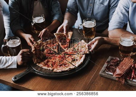 Close Up Of People Hands Taking Slices Of Pizza. Smiling Friends Eating Pizza And Drinking Beer At R