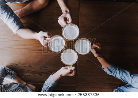 Top View Of Friends Clinking Glasses Beer At Pub. Happy Friends Drinking Beer And Clinking Glasses A