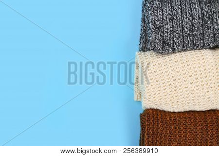 Warm knitted sweaters. Pile of knitted clothes on blue background, sweaters, knitwear, space for text, Autumn winter concept. Top view. poster