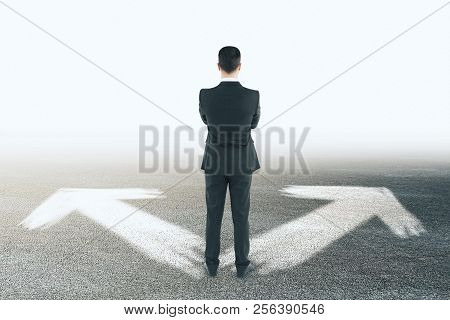 Businessman With Arrows On Concrete Background. Different Direction And Choice Concept