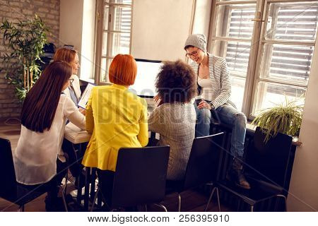 Modern informal working team at work on computer together