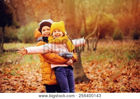 Autumn Portrait Of Happy Kids Playing Outdoor In Park. Smiling Brother And Sister Walking In Sunny D