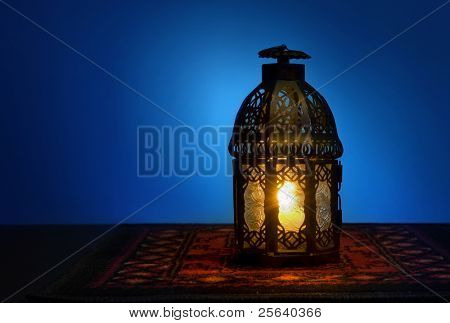 An illuminated Arabic lantern on blue background