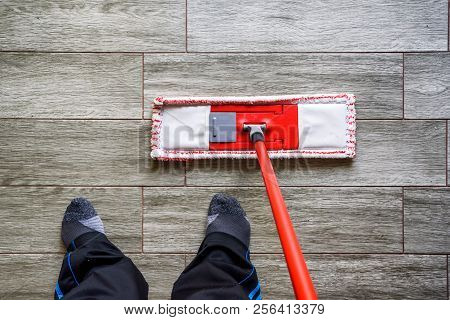 High Angle View Of Person Cleaning Tiles Floor With Mop