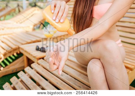 Cut View Of Girl Sitting On Sunbed. She Has Crossed Legs And Put Some Sun Protection Lotion On Hand.