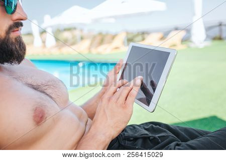 Cut View Of Bearded Guy Sits On Sunbed And Wears Glasses. He Holds White Tablet And Looks At It. He