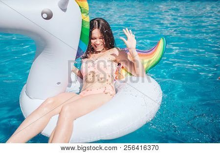 Attractive And Beautiful Woman Is Lying On Air Mattress In Swimming Pool. She Holds Hand In Air. Gir