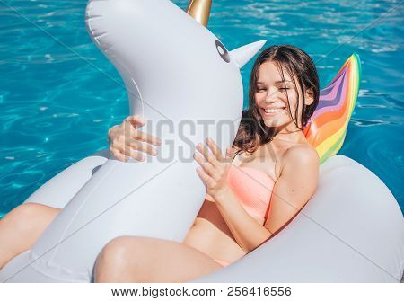 Nice And Beautiful Girl Is Lying On Air Mattress. It Has Shape Of Unicorn. Girl Holds It With Both H