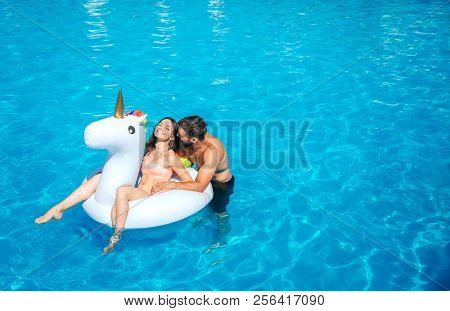 Nice And Positive Picture Of Man And Woman Swimming In Pool. Girl Sits On Air Mattress. She Is Laugh
