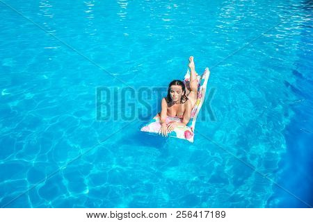 Nice And Well-built Girl Is Lying On Air Mattress And Getting Some Tan From Sun. She Is Serious And