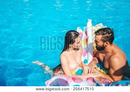 Couple Is Standing In Swimming Pool And Look At Each Other. They Are Wet. Couple Leans To Air Mattre