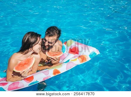 Cute Picutre Of Young Man And Woman Leaning To Air Mattress And Hold Pieces Of Watermelon. They Look