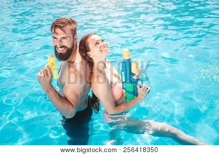 Funny Couple Stands In Swimming Pool. They Pose And Smile. Girl Looks Up. They Hold Water Guns In Ha