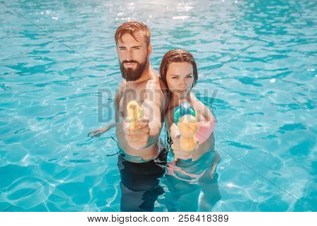 Serious And Concentrated Couple Stands Back To Back In Swiming Pool And Look On Camera. They Pose. G