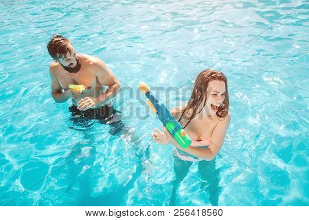 A Picture Of Guy Attacking Girl In Swimming Pool. He Is Shooting From Water Gun. Girl Is Trying To D