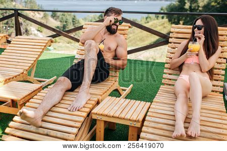 Nice And Positive Couple Is Lying On Sunbeds And Hold Cocktails In Hands. They Look At Each Other An
