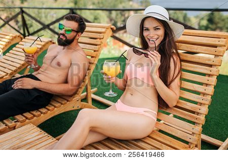 Sexy and hot girl sits on sunbed and looks on camera. She bites sunglasses and hold glass of cocktail in hand. Guy sits calm and relax. poster