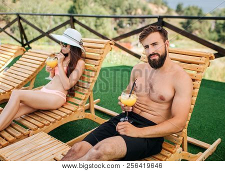 Wel0built And Handsome Guy Sits On Sunbed And Looks On Camera. He Holds Glass On Cocktail In Hands.