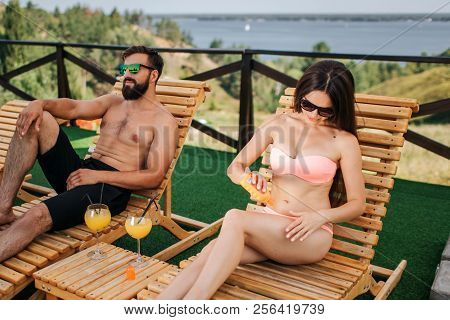 Beautiful Couple Sit On Sunbeds And Chilling. Girl Put Some Cream Protection On Skin And Rub It. Guy