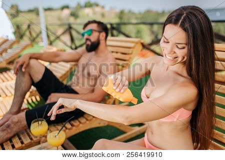 Nice And Positive Girl Sits And Puts Some Sunproof Cream On Skin. She Holds Orange Bottle In Right H