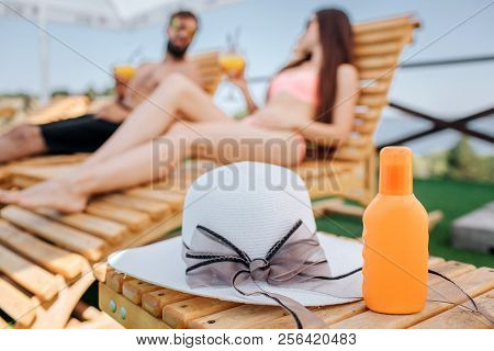 A Picture Of Orange Bottle And Hat Lying On Small Wood Table. Couple Is Sitting Behind It. They Look