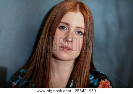 Closeup portrait of serious teenage ginger girl looking at camera.