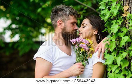 Gentle kiss. Man bearded hipster hugs gorgeous girlfriend. Pleasant romantic kiss. Couple love romantic date nature park background. Love relations romantic feelings. Couple in love going to kiss poster