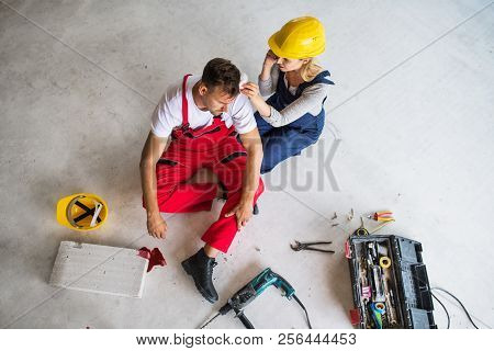 A Woman With Smartphone Helping Man Worker After An Accident At The Construction Site.