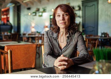 Mature Woman Sitting In Restaurant, Portrait Indoor