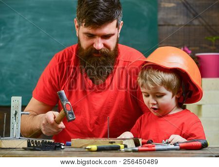 Boy, Child Busy In Protective Helmet Learning To Hammering Hobnails With Dad. Workshop And Handyman